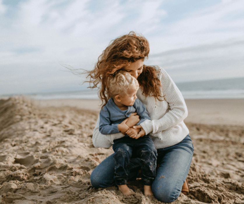 woman hugging her son on beach releases most compassionate self